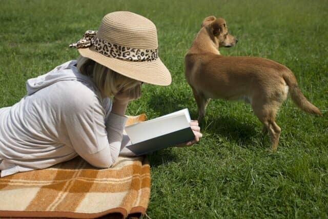 芝生でパーカーを着る女性