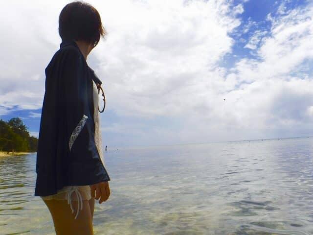 海辺でパーカーを着る女性