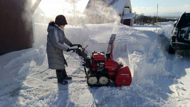除雪機を使う女性