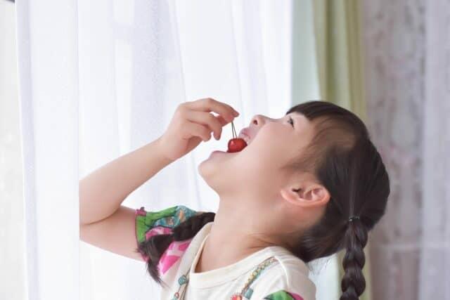 さくらんぼをたべる少女