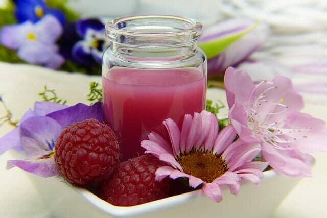 花と一緒に盛られたラズベリーとラズベリージュース