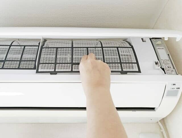 エアコンのフィルターを外している手