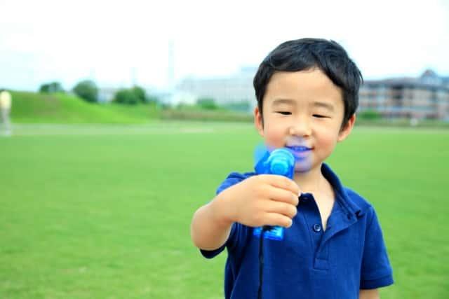 小型扇風機を持つ少年