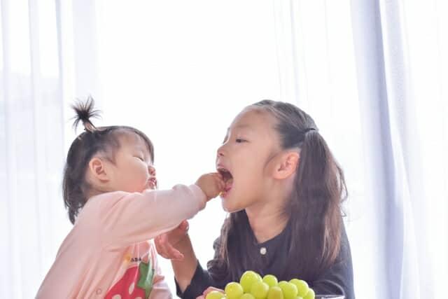 子供同士が皮ごとぶどうを食べる