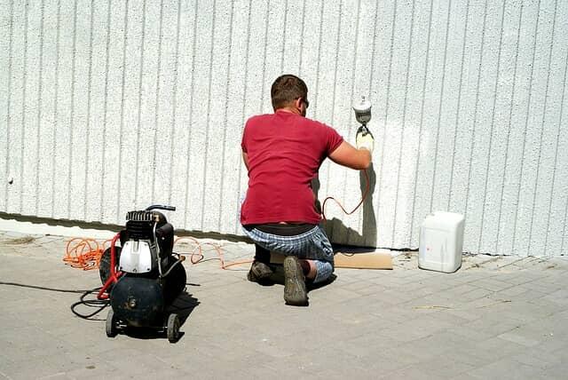 スプレーガンで壁を塗装する男性