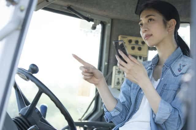農機の中でスマートフォンを操作する女性