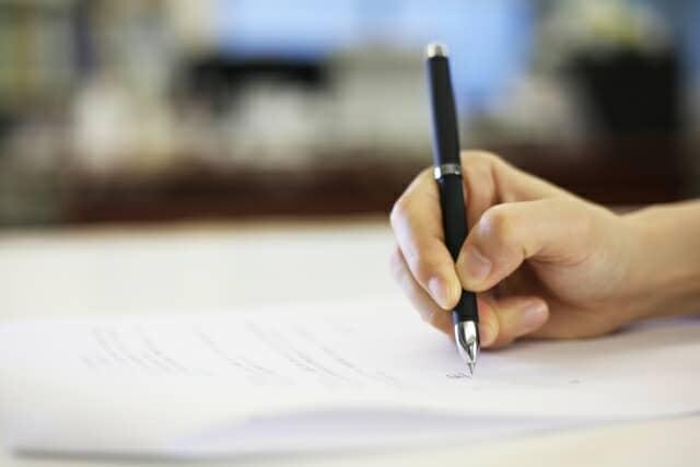 紙に字を書いている手