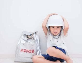 非常持ち出し袋と防災ヘルメットをかぶる子ども