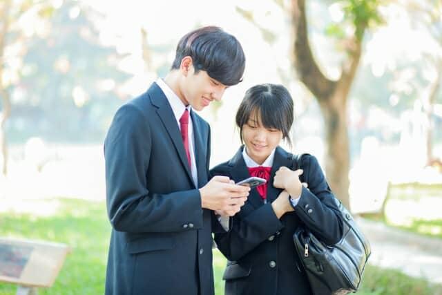 携帯を見る高校生
