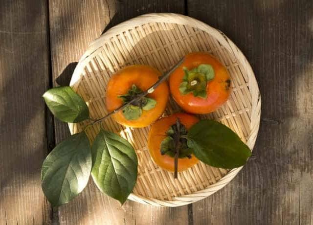 ザルの上二、葉と枝が付いた採れたての柿が3つ