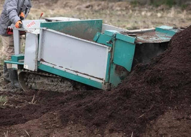 土の山から土を農作業機械で移動する