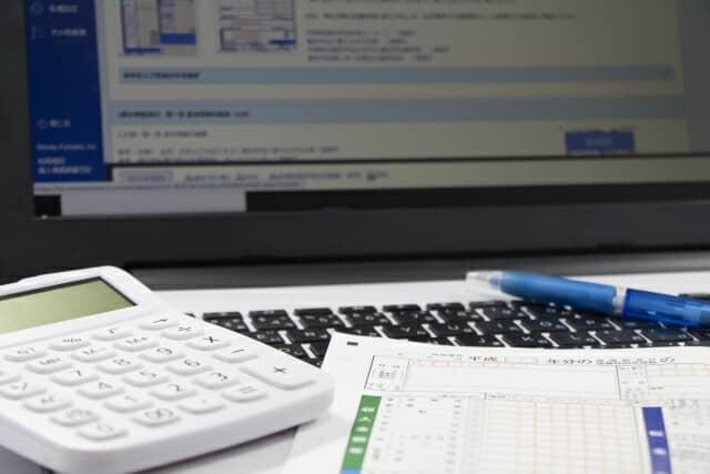 パソコンと電卓と書類