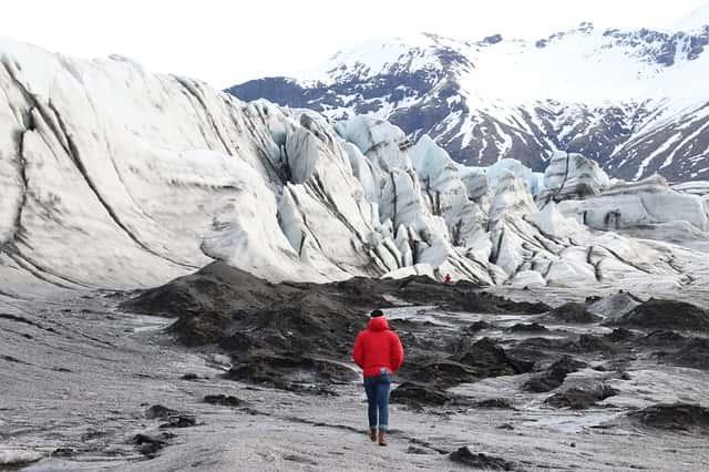 ウィンドブレーカーを着て雪山を歩く男性