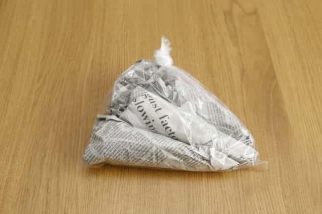 新聞紙で包みポリ袋に入れた人参