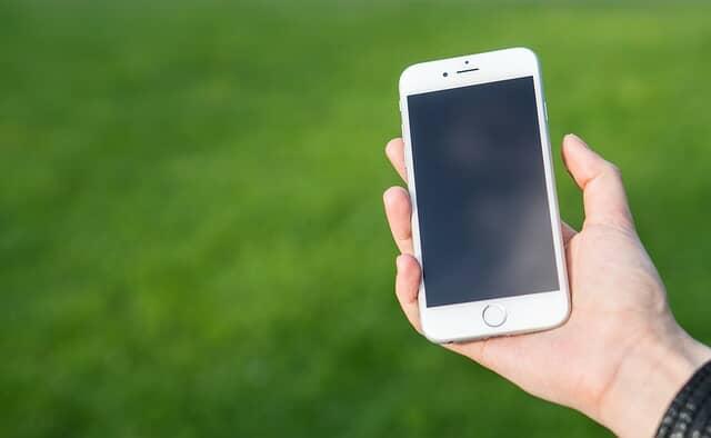 畑でスマートフォンを操作