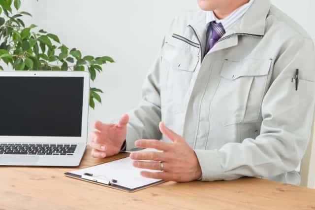 作業着を着て説明する男性