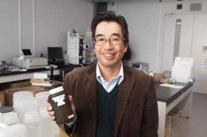原料となるコーヒー粕を手にする河原先生