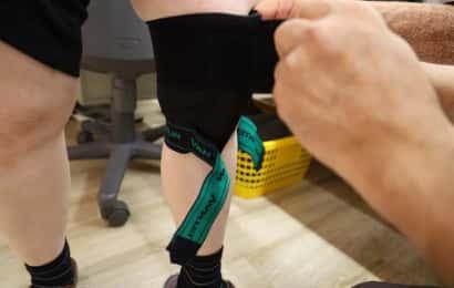 膝サポーターの上部ベルトを巻いているところ