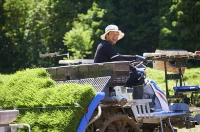 トラクターに乗って田植作業をする人