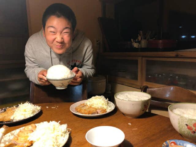 大盛りのご飯を持って笑う少年