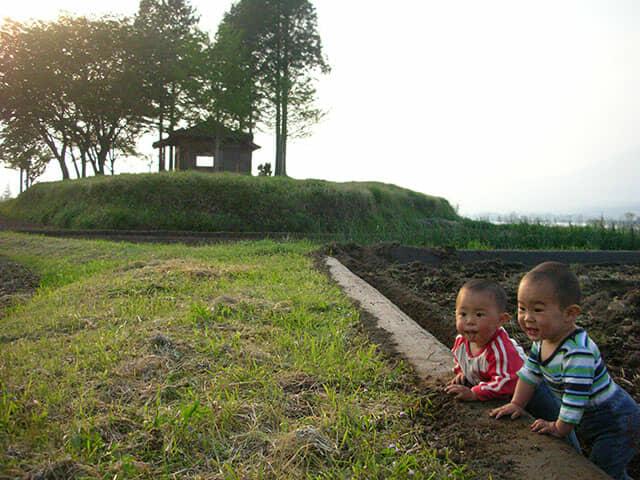 畑にいる男の赤ちゃん2人