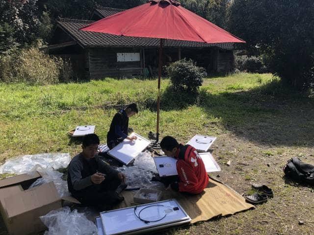 外でソーラーパネルを作る少年たち