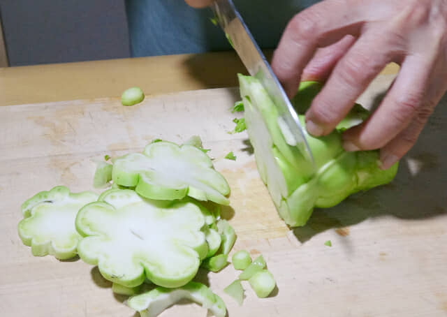 収穫したザーサイを包丁でスライスする