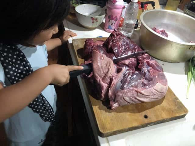 イノシシ肉を切る女の子