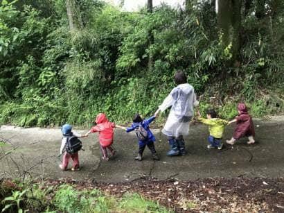 山道を手をつないで歩く子どもたち