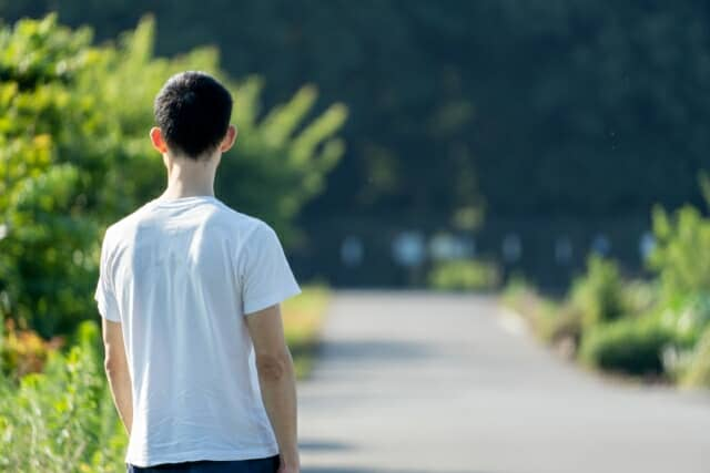 道でたたずむ男性の後ろ姿