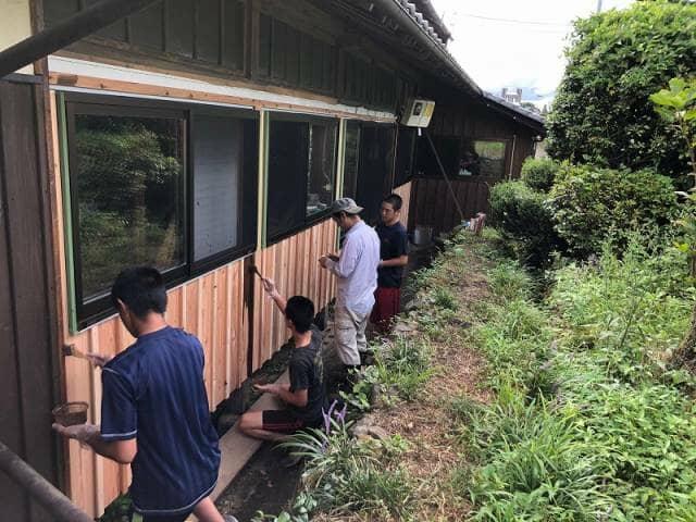 家の壁にペンキ塗りをする男の人たち