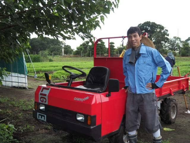 トラクターの前に立つ飯田さん