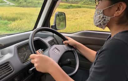 軽トラックを運転するマスクをした女性