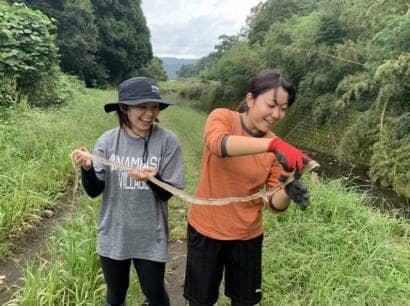 蛇の抜け殻を手にとる女性2人