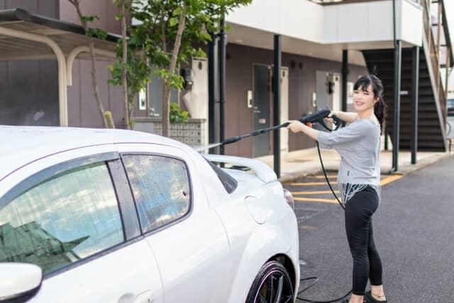 高圧洗浄機で洗車する女性