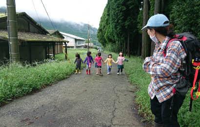 散歩する子どもたちと見守る女性