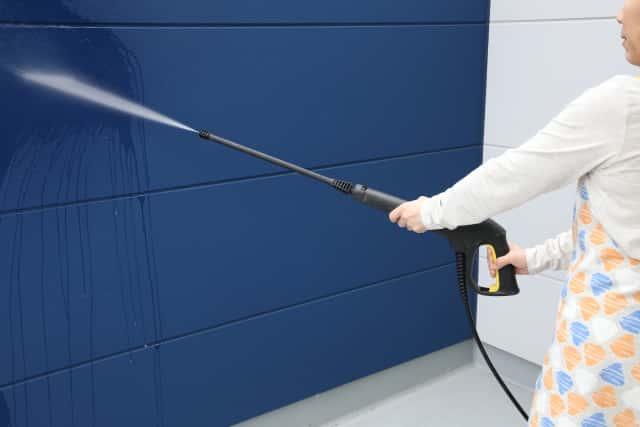 家の外壁を高圧洗浄機で掃除する人