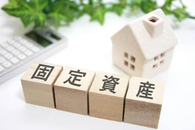 固定資産と書かれた積木