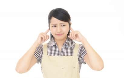 耳を塞ぐ女性