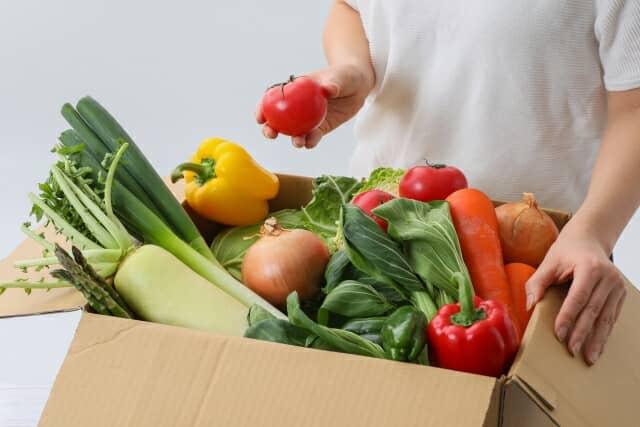 野菜の箱と野菜を持つ手