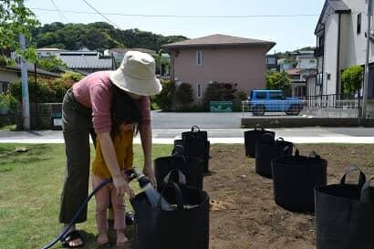 土に水を与える親子