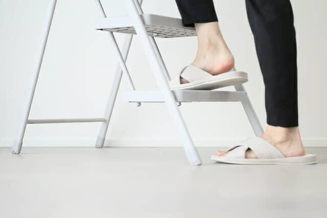 脚立に登る女性の足元