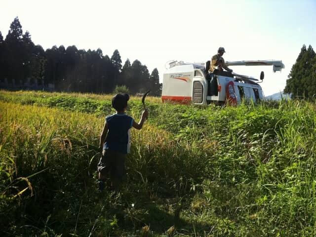 草刈りする少年