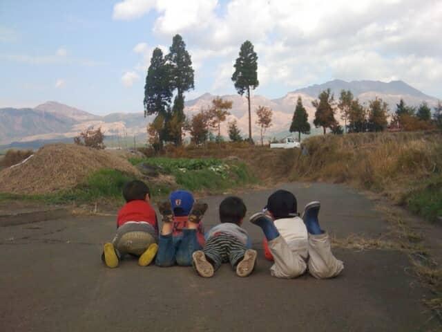 道路にうつぶせになる子ども達